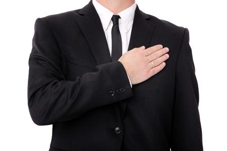 Un'immagine di un uomo elegante con la sua mano disposta sul cuore sopra fondo bianco Archivio Fotografico