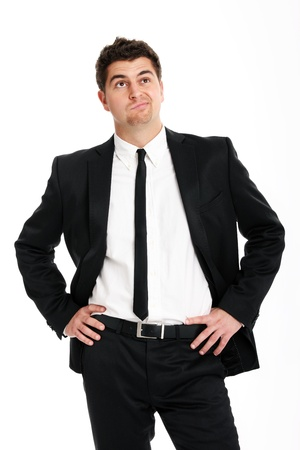 A picture of a young handsome undecided businessman standing over white background photo