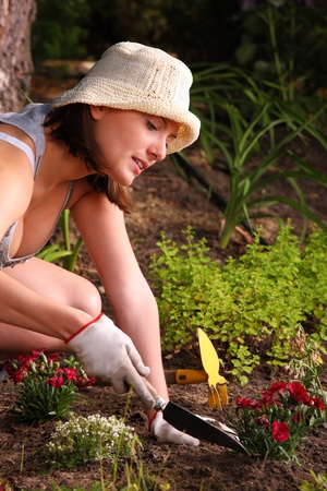 A picture of a young happy woman tending flowers in the garden photo