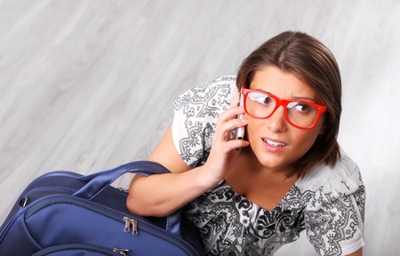 A picture of a young irritated woman talking on the phone at the airport photo