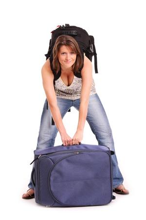 femme valise: Une photo d'une jeune femme qui tente de soulever une valise lourde sur fond blanc Banque d'images