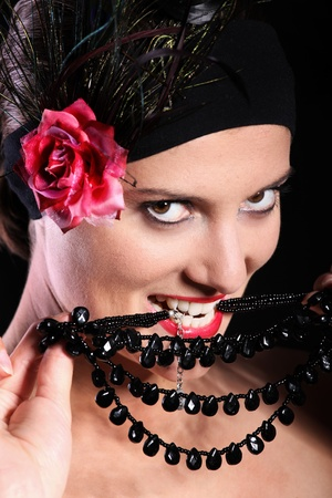 A picture of a seductive woman in red lipstick biting a necklace over black background photo