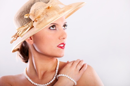 A picture of a beautiful woman in a red lipstick, pearls and a hat over white background photo