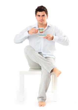 look pleased: young man sitting on a coffee table with cup of coffee in hand over white background
