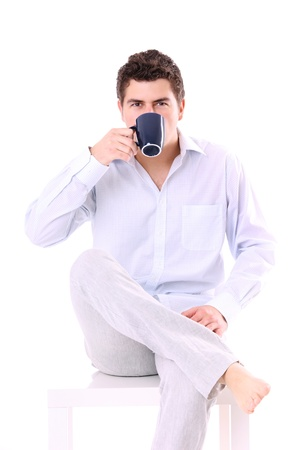 A picture of a young man sitting on a chair with coffee over white background photo