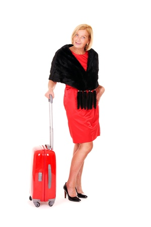 A picture of an attractive woman in her fifties standing over white background with a suitcase Stock Photo - 10057512