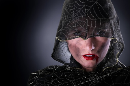 A portrait of a hooded female vampire standing against dark background photo