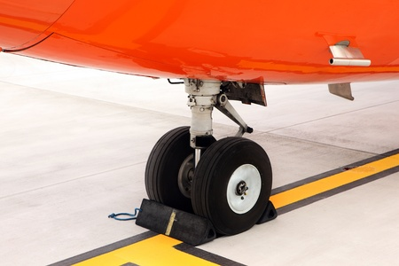 airport runway: A picture of an orange undercarriage of a business jet standing on the apron