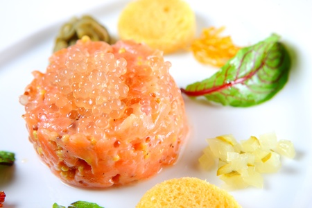 l natural: A close-up of a portion of salmon tatar with caviar served on a white plate Stock Photo