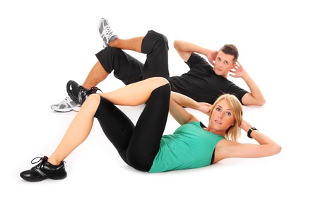 A picture of a young couple doing sit-ups over white background photo