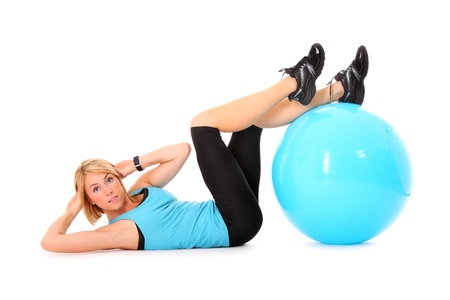 A picture of a beautiful young woman doing sit-ups with a ball over white background Stock Photo - 10652462