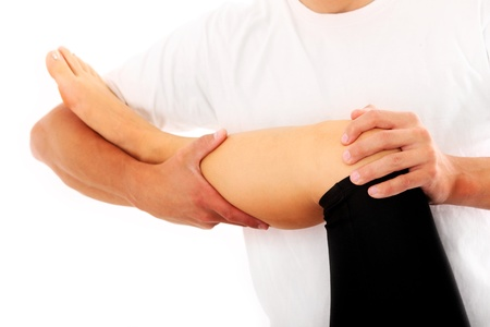 A picture of a physio therapist trying to fix the leg over white background Stock Photo - 10652461