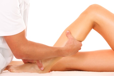 A picture of a physio therapist trying to fix the leg over white background Stock Photo - 10652463
