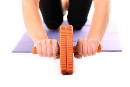 gripe: A close-up of a young woman training with AB wheel over white backgrouns Stock Photo
