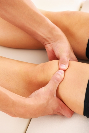 A picture of a physio therapist giving knee massage over white background photo