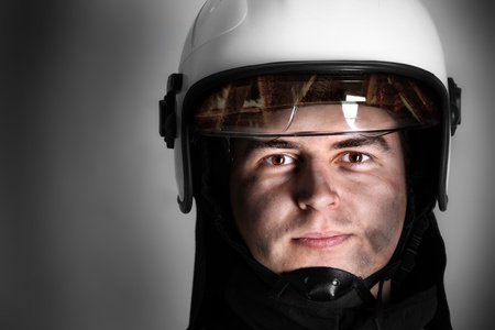 emergency vest: A picture of a young firefighter in a white helmet looking against grey background