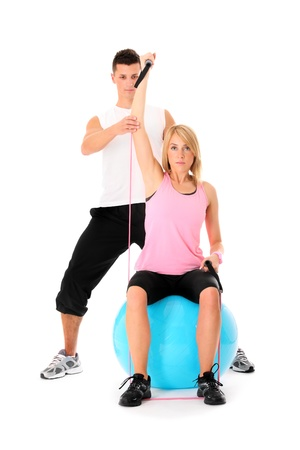 A picture of a young woman working out with her personal trainer over white background Stock Photo - 11042530