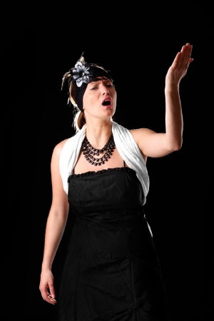 A picture of a young beautiful opera singer performing over black background photo