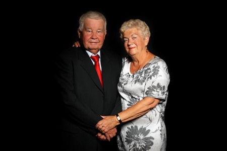 70s adult: A portrait of a beautiful senior couple standing together over black background Stock Photo
