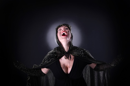 A portrait of a hooded female vampire standing against black background photo