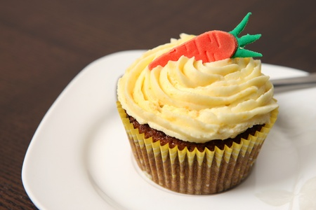carrot cake: A picture of a carrot cupcake served on a white plate