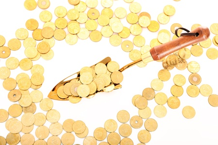 A picture of a small shovel full of golden coins over white background Stock Photo - 11348624