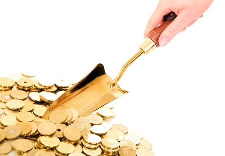 golden shovel: A picture of a hand with small shovel taking golden coins from a pile over white background Stock Photo