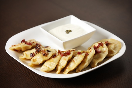 A picture of Polish pierogi with pork scratchings and sour cream served on a white plate photo