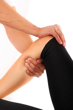 A picture of a physio therapist trying to fix the leg over white background photo