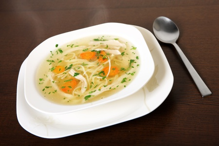 polish chicken: A picture of a bowl of traditional Polish chicken soup served in a bowl over wooden background