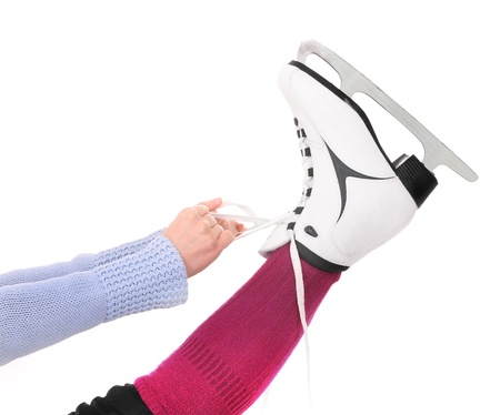 A picture of a woman tying her skates over white background photo