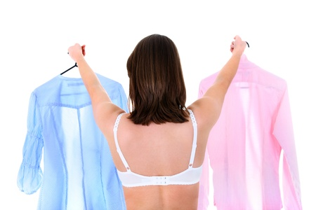 A portrait of a young woman trying to decide between two shirts over white background photo