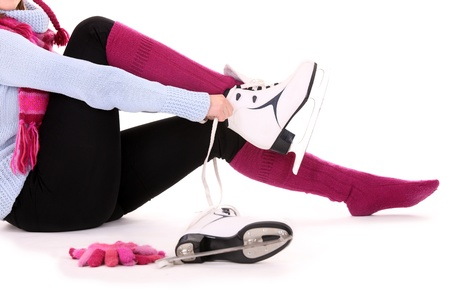 A picture of a woman putting on her skates over white background photo