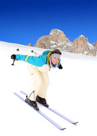 A picture of a young happy woman skiing in the Alpes photo