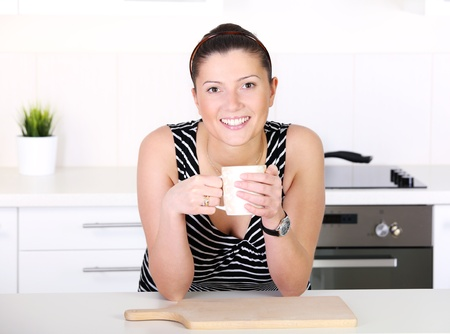 A picture of a young woman with morning coffee in the kitchen Stock Photo - 12007275