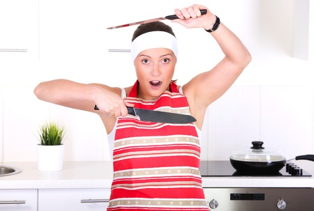 holding a knife: A portrait of a young beautiful wife working in a modern kitchen