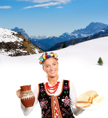A portrait of a beautiful and hospitable Polish woman in a traditional outfit over mountain background Stock Photo - 12198587