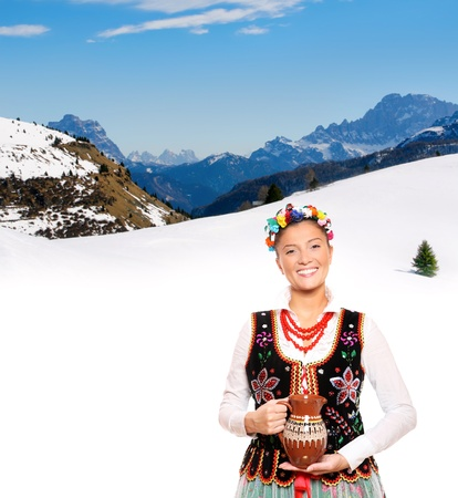 A portrait of a beautiful and hospitable Polish woman in a traditional outfit over mountains in winter Stock Photo - 12198585