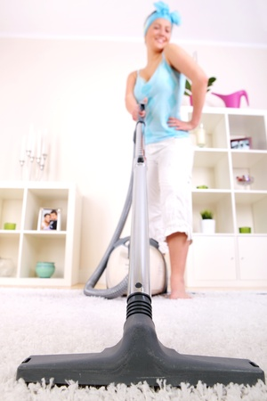 A picture of a young wife hoovering her apartment photo