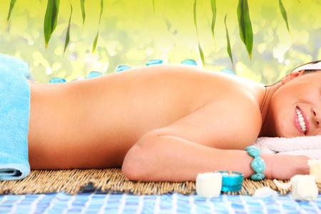 A picture of a young beautiful woman having stone massage in exotic spa centre photo