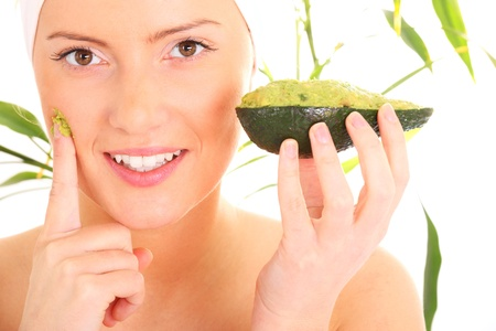 avocado: Un ritratto di una giovane donna applicazione maschera di avocado naturale sul viso