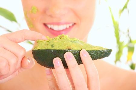 aguacate: Un retrato de una mujer joven de aplicar la m�scara de aguacate natural, en su cara