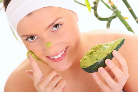 A portrait of a young woman applying natural avocado mask on her face photo
