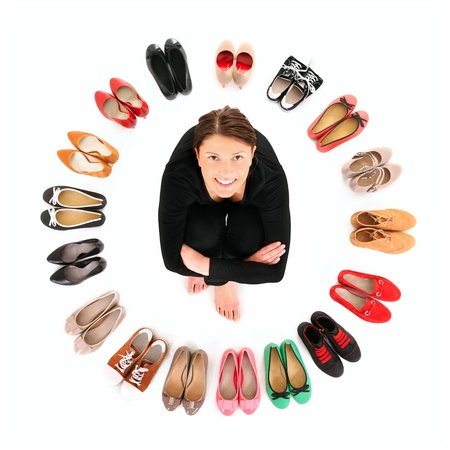 A picture of a pretty young woman sitting in the circle of shoes over white background Stock Photo - 12612344
