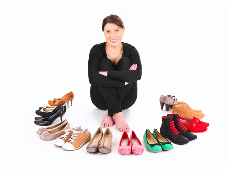 A picture of a pretty young woman sitting in the circle of shoes over white background photo