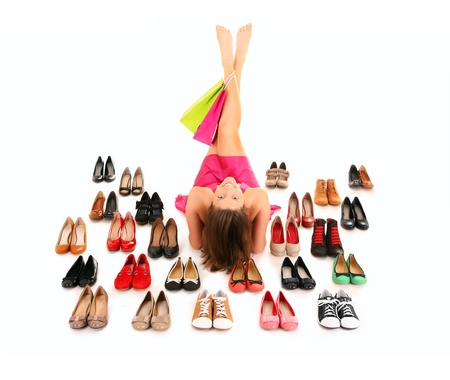 A picture of a pretty young woman lying among shoes over white background photo