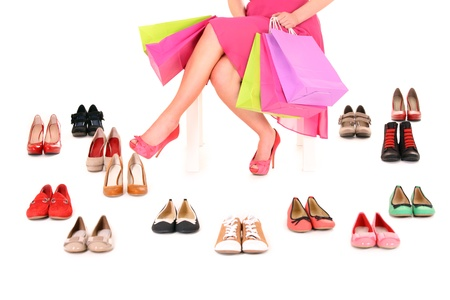 A picture of a young woman sitting with shopping bags among shoes over white background Stock Photo - 12612313