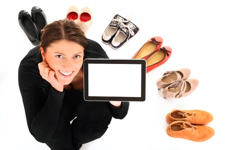 A picture of a pretty young woman sitting in the circle of shoes with tablet over white background Stock Photo - 12612305