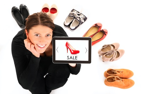 A picture of a pretty young woman sitting in the circle of shoes with tablet over white background photo