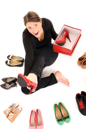 A picture of a young woman trying on new pair of heels over white background photo